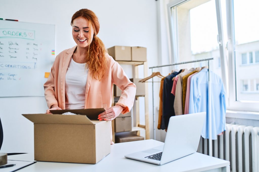 Young small business owner packing sold items and preparing deliveries